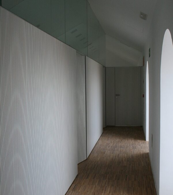 Acoustic wall paneling finished on white melamine with flush-to-wall doors