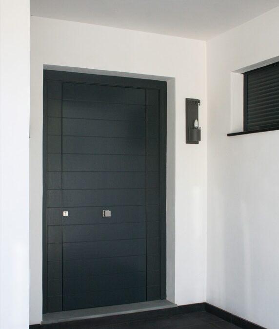 Puerta exterior con lamas horizontales acabada en laca gris antracita