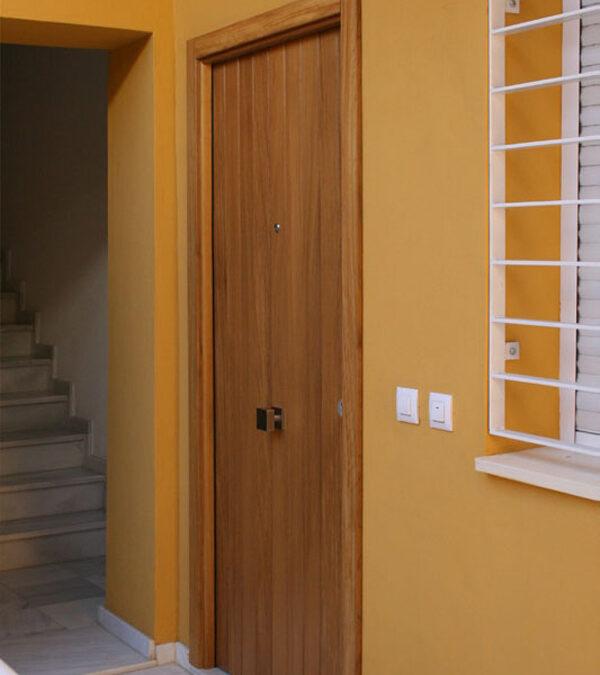 Puerta de entrada con lamas verticales en madera maciza de iroko