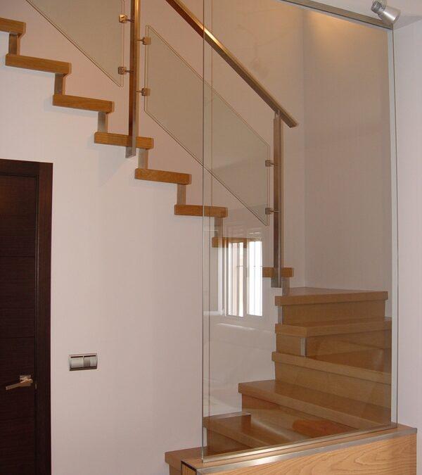 Revestimiento de escalera con pavimento laminado enroble, barandilla de acero inoxidable y vidrio
