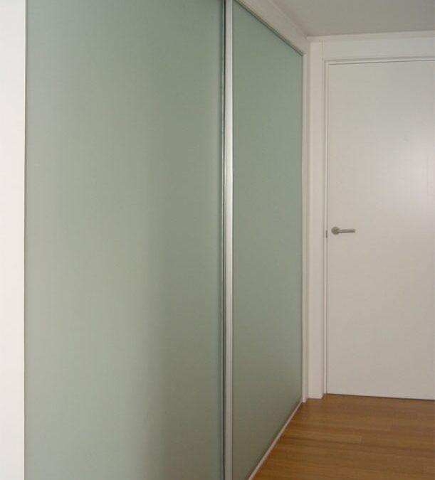 Armario empotrado a medida con puertas correderas con esmalte vidriado y perfilería de aluminio anodizado
