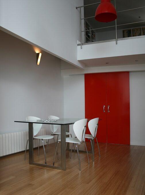Puertas correderas de suelo a techo acabadas en laca roja mate