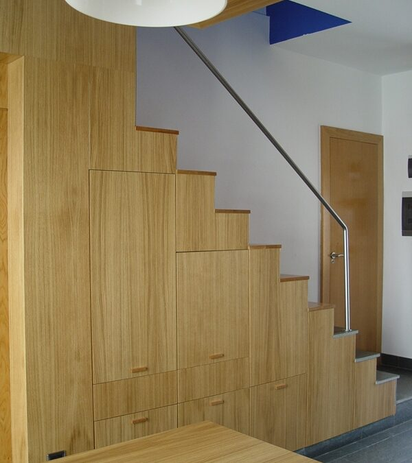 Stair-storage area completed in varnished oak, stainless steel handrail.