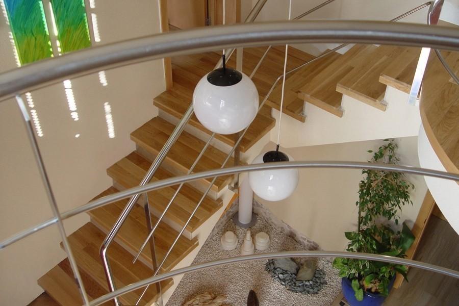 Revestimiento de huellas de escalera con lamas roble, barandilla de acero inoxidable
