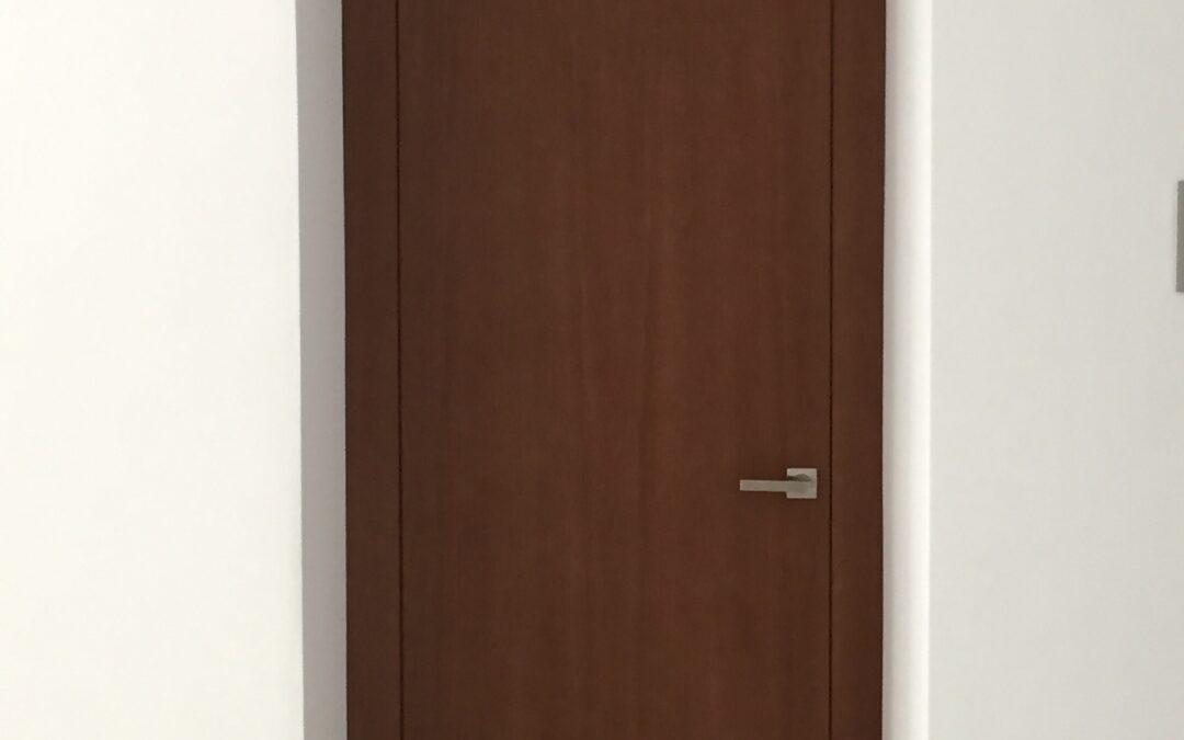 Puerta enrasada con montante en Nogal
