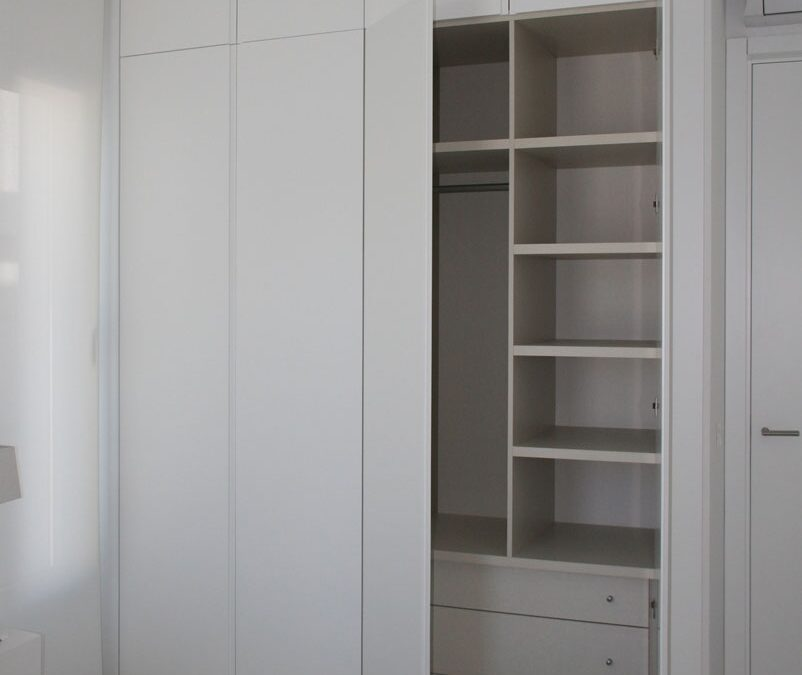 Custom wardrobe made of white laquered doors and textil melamine interior