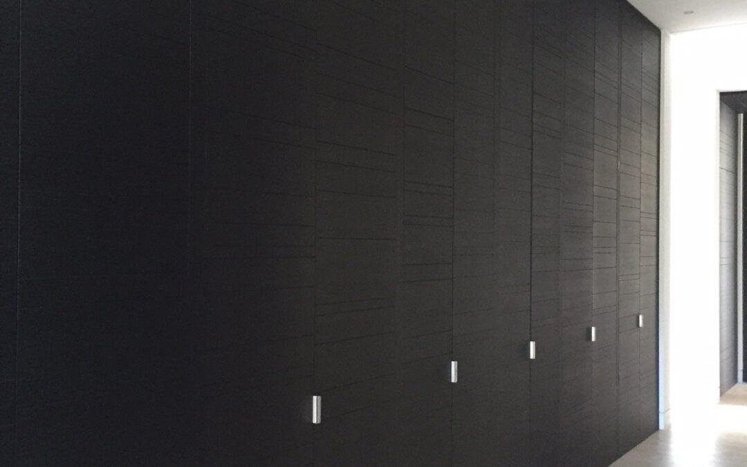 Frente de armario de suelo a techo con puertas ranuradas en madera de wengué