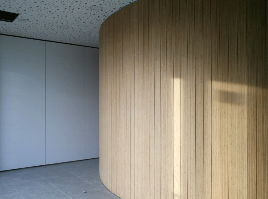 Curved wall paneling with carbonized vertical bamboo slotted boards